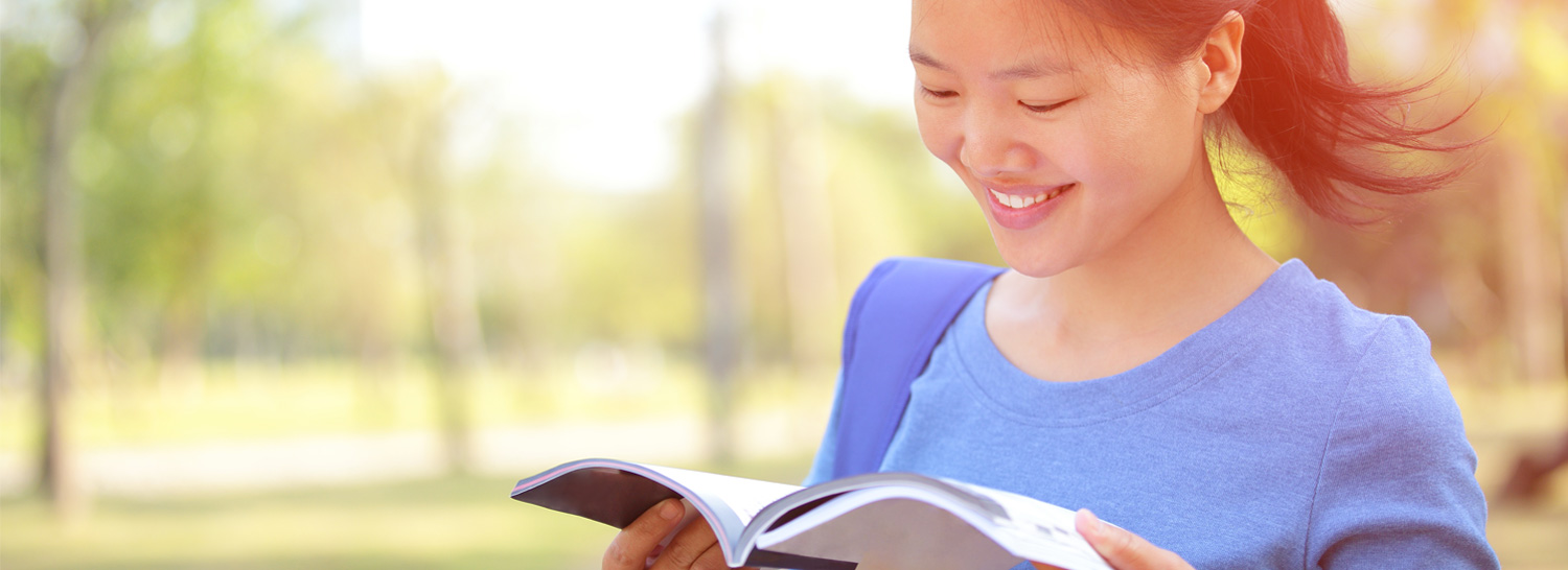 Woman smiling while reading a book.
